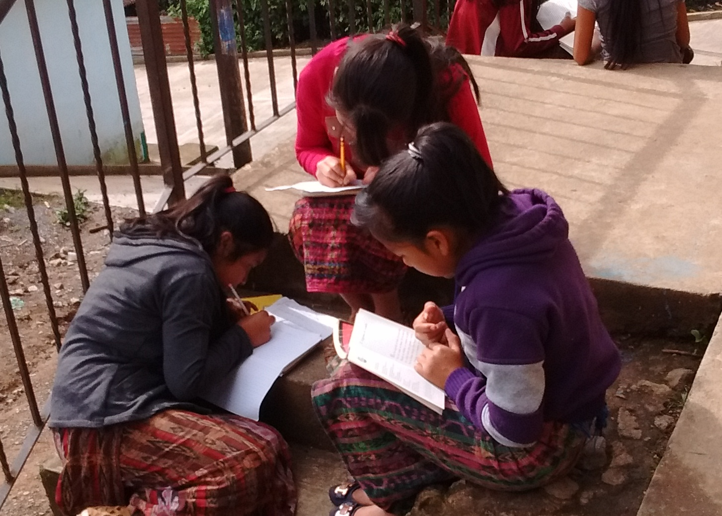Students work on a writing assignment on the front steps of the school.