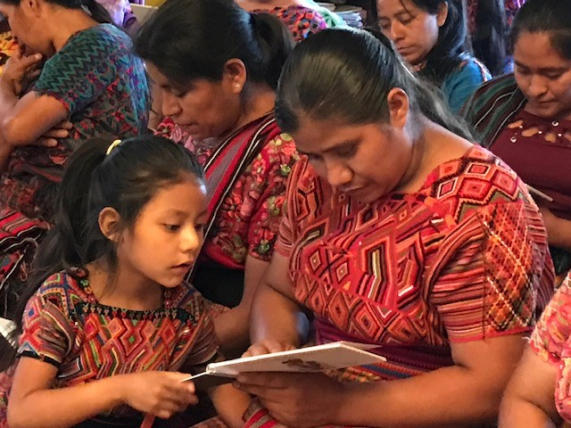 A mother and daughter browse a new Ixil book before a school assembly.